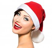 Christmas Woman. Beauty and Sexy Model Girl in Santa Hat isolated on White Background. Funny Laughing Surprised Woman Portrait. Open Mouth. True Emotions. Red Lips and  Beautiful Holiday Makeup.