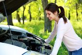Happy woman looks under hood car background green park