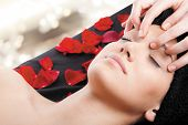 Beautiful woman receiving a facial massage lying on bed with rose petals.