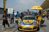SEPANG, MALAYSIA - MAY 11, 2014: The Singha Porsche AAS Team grid girl poses with the team car, a Po