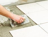 picture of grout  - Bathroom ceramic floor tiling by manual worker - JPG