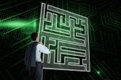 Composite image of maze and businessman looking against green and black circuit board