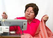 old  Woman Using Sewing Machine At Home