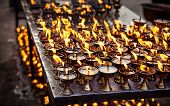 stock photo of nepali  - Butter lamps with flames near Bodhnath stupa in Kathmandu valley Nepal - JPG