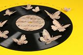Old vinyl record with paper butterflies, on yellow background