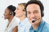 Happy Customer With Headsets Working With Other Colleague In Call Center