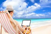 Relaxed Man Sitting On Beach Chairs And Using A Laptop.