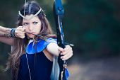 stock photo of hunters  - fictional forest hunter girl with bow and arrow - JPG