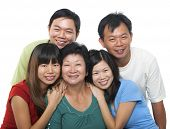 Asian family portrait. Happy senior mother and her adult offsprings, smiling isolated on white background.