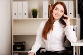 woman sitting and talking on phone in office