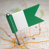 Nigeria Small Flag on a Map Background.