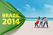 stock photo of pulling  - Group of people pull soccer a championship banner of the year 2014 at brazil - JPG