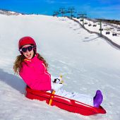 Kid girl playing sled in winter snow with helmet and goggles