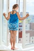 Girl Teenager Standing On Window With Opened Door, Looking Down From Height