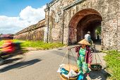 pic of conic  - Asian woman in traditional conical hat carrying baskets at Hue city citadel gates in Vietnam Asia - JPG