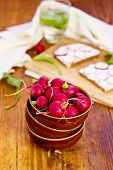 Bowl full of Radishes on the wooden background