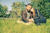 image of two women taking cell phone  - Couple sitting on grass after a romantic tour with bicycle  - JPG