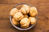Walnuts on wooden bowl on top