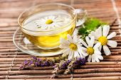 Cup of herbal tea with chamomile flowers on wooden background