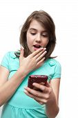 Shocked teen girl covering her mouth while reading sms (mms)