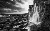 Beautiful Landscape Image Waterfall Flowing Into Rocks On Beach At Sunset  Black And White