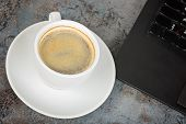 Shot of cup of coffee and kayboard