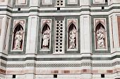 four statues in niches on Bell Tower on Piazza del Duomo in Florence in Italy