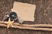 Paper, compass, rope and seashell on the old wooden background
