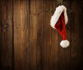 Christmas Santa Claus Hat Hanging On Wood Wall, Xmas Concept, Decoration, Grunge Wooden Backgroud