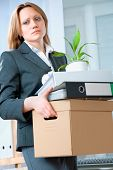 stock photo of unemployed people  - A fired woman in a suit carrying a box of personal items - JPG