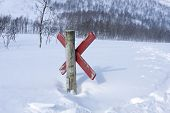 picture of nordic skiing  - Red wooden cross along a trail in deep snow - JPG