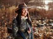 pic of shotgun  - Waterfowl hunting the female hunter carry a shotgun autumnal bushes on background - JPG
