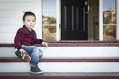 Cute Melancholy Mixed Race Boy Sitting on Front Porch Steps.