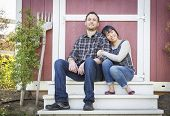 Happy Mixed Race Couple Relaxing on the Steps of Their Barn.