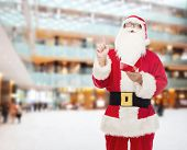christmas, holidays, gesture and people concept - man in costume of santa claus with notepad pointing finger up over shopping center background