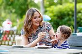 stock photo of little young child children girl toddler  - Young mother relaxing together with her little child adorable toddler girl in summer outdoors cafe drinking coffee and eating muffin or cupcke - JPG