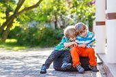 stock photo of little kids  - Two little sibling kid boys hugging and having fun outdoors in home - JPG