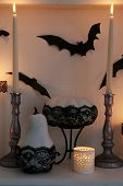 Halloween composition on fireplace on white wall background