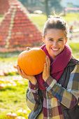 Portrait Of Smiling Young Woman Showing Pumpkin