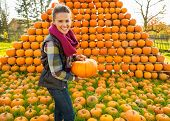 Portrait Of Smiling Young Woman Holding Pumpkin In Front Of Pump