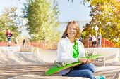 Smiling girl holds skateboard, sits in playground