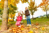 picture of swing  - Happy girl sitting on swings and blond boy standing near holding the ropes of swings in park during autumn sunny day - JPG