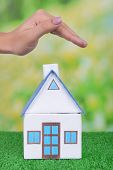 Small house with woman hand on grass on bright background