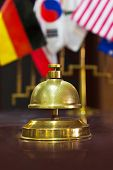 Service ring bell on a hotel reception and flags on background