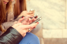 image of chat  - Girls typing on mobile phones  - JPG