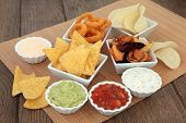 stock photo of crisps  - Crisp and dip party food selection in porcelain bowls over bamboo and oak - JPG