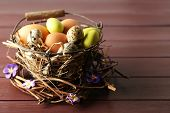 picture of bird egg  - Bird eggs in wicker basket with decorative flowers on color wooden background - JPG
