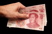 picture of yuan  - Modern Chinese 100 yuan renminbi banknotes in male hand isolated on black background - JPG