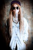 stock photo of dreadlocks  - Modern teenage girl with blonde dreadlocks over grunge background - JPG