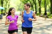 Running couple training in Central Park, New York City (NYC). Happy runners talking together during  poster
